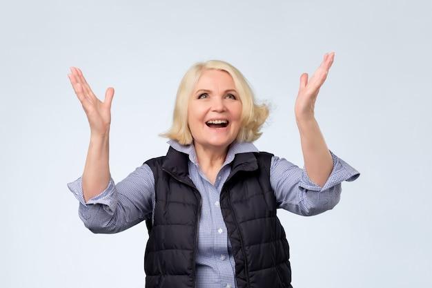 肯定的な感情のために手を上げる年配の女性