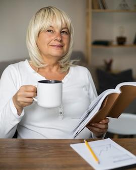 Donna anziana che legge un libro per la sua prossima lezione