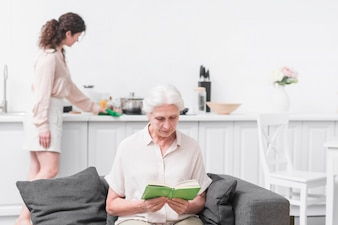 Senior woman reading book in front of woman doing housekeeping work