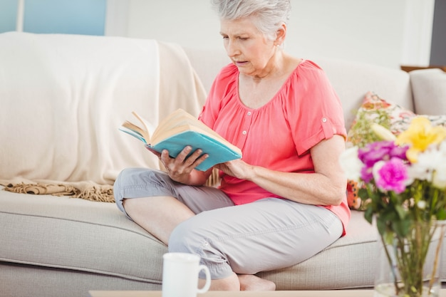 Senior woman reading a book in living room