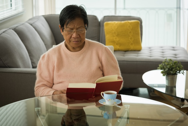 Senior woman reading book at table
