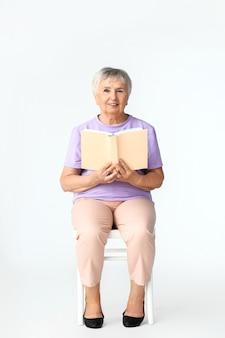 Старшая женщина, читающая книгу