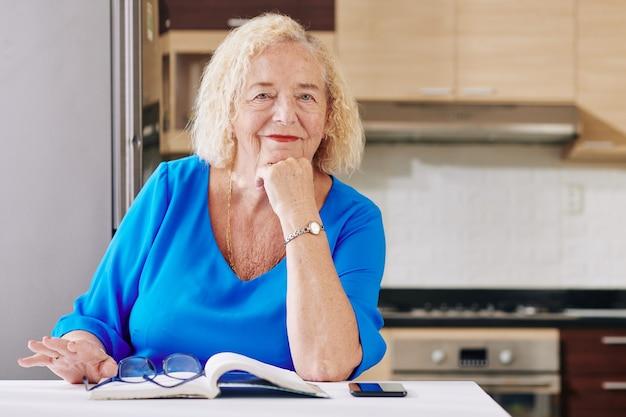年配の女性が台所で読書