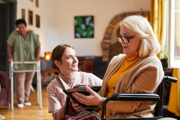 Старшая женщина читает в доме престарелых