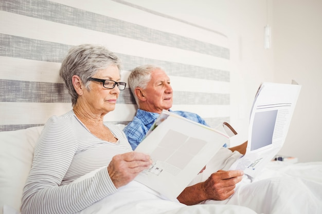 Senior woman reading magazine and senior man reading newspaper on bed