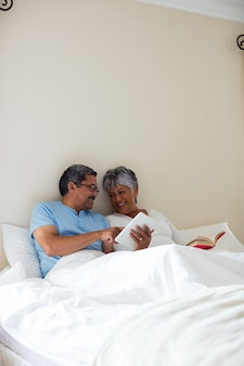 Senior woman reading a novel and senior man using digital tablet on bed