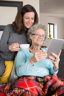Senior woman reading online book together with adult daughter