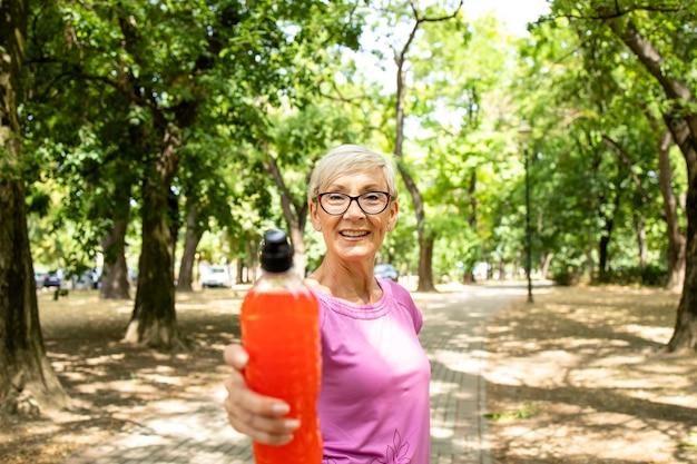 공원에서 에너지 음료를 들고 훈련할 준비가 된 고위 여자.