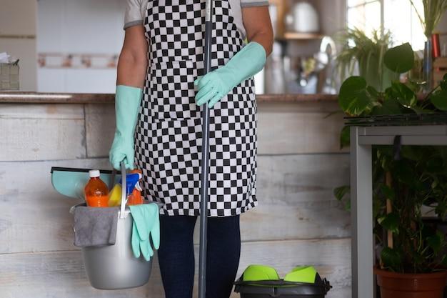 家事を始める準備ができている年配の女性。彼女の近くにクリーニング製品が入ったプラスチック製のバケツ