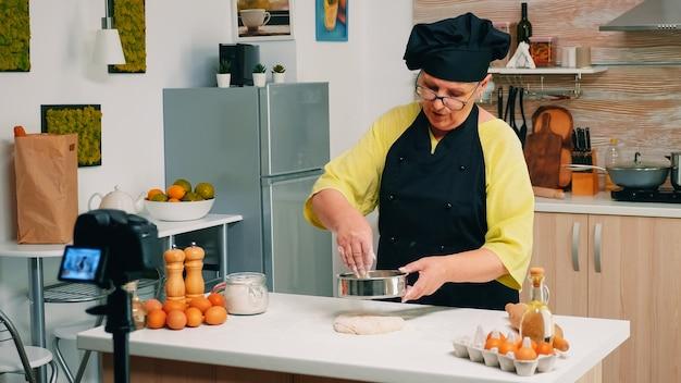 Старшая женщина записывает живое видео для кулинарного видеоблога дома. блогер на пенсии, повар, влиятельный человек, используя интернет-технологии, общается, ведет блог в социальных сетях с помощью цифрового оборудования.
