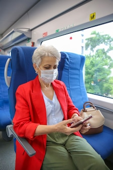Senior woman in a red jacket and a medical mask rides a train