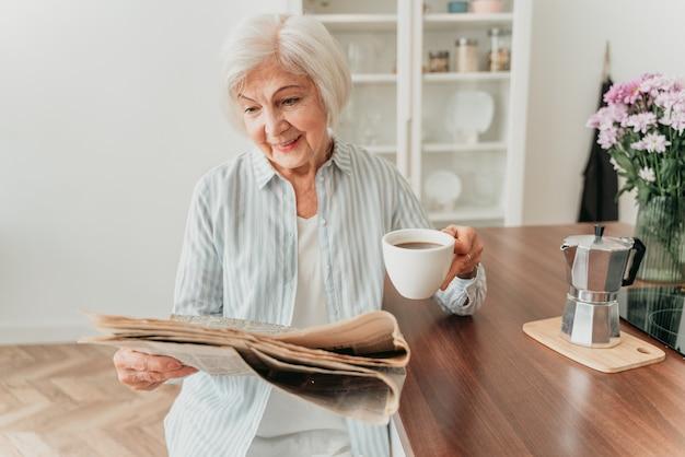 집에서 휴식을 취하고 신문을 읽고 아침 식사를 하는 노인 여성