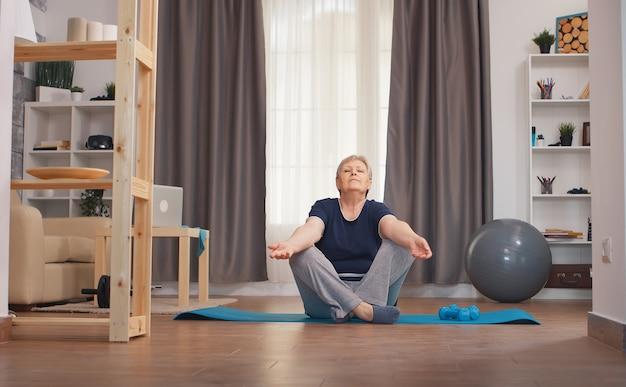 ヨガをしているリビングルームでリラックスした年配の女性。アクティブで健康的なライフスタイルスポーティな老人トレーニングトレーニングホームウェルネスと屋内運動