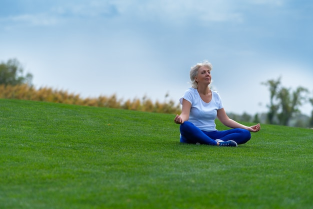 명상하는 동안 푸른 잔디에 편안한 고위 여자