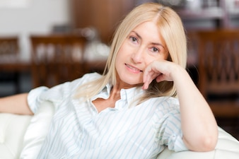Senior Woman Relaxing On Sofa At Home