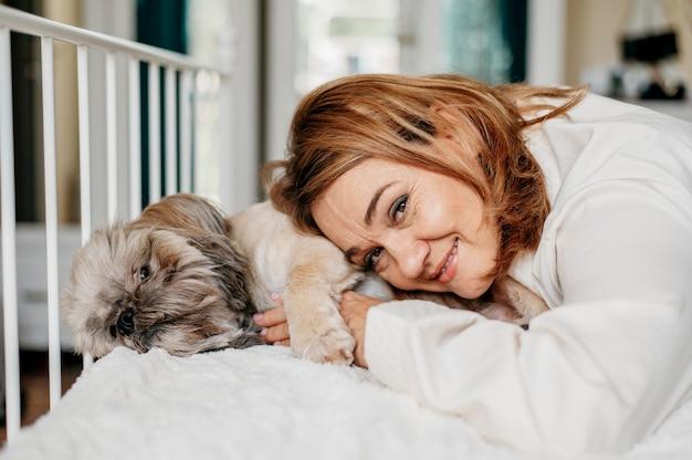 Старшая женщина, расслабляющаяся со своей собакой