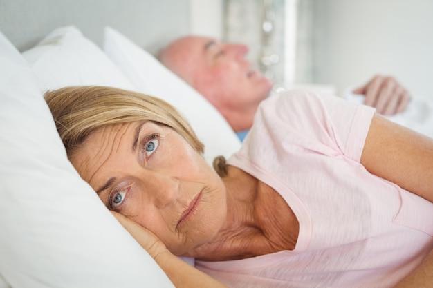 Женщина старшия кровати отдыхая