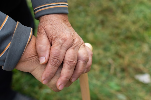 Senior woman resting on a wooden walking stick