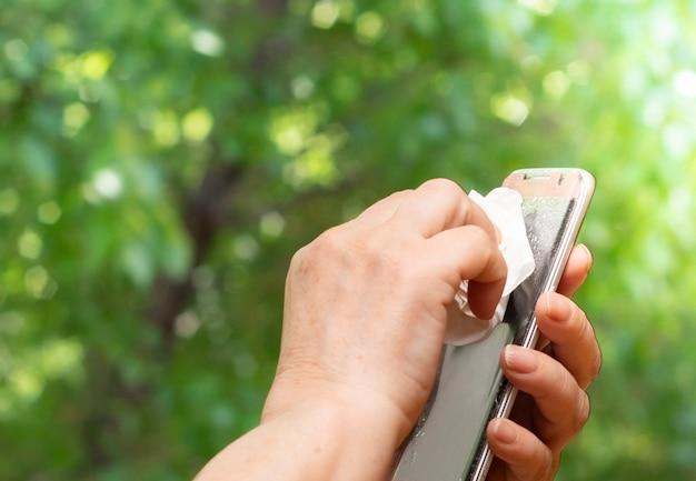 Рука старшей женщины распыляет спирт, распыляет дезинфицирующее средство на мобильный телефон