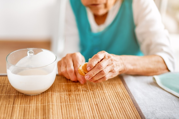 Руки старшей женщины, держа большую чашку йогурта