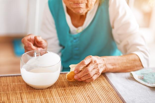 Senior woman's hands holding big cup of yogurt