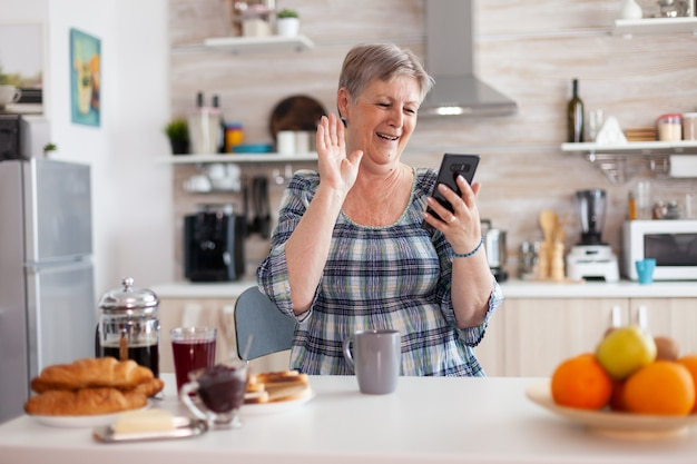 Senior woman saying hello while having video call with family using smartphone in kitchen during breakfast. elderly person using internet online chat tech, tablet webcam for virtual conference call