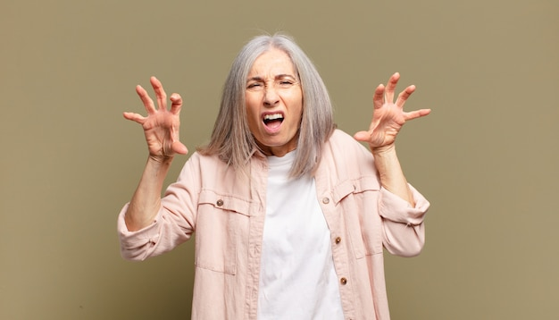 Пожилая женщина кричит от паники или гнева, шокирована, напугана или разъярена, положив руки на голову
