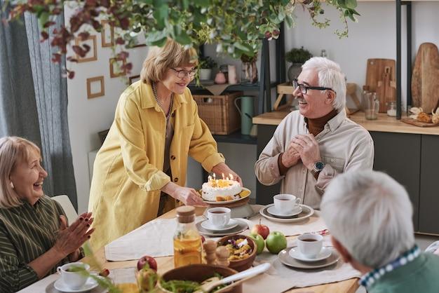 彼らが家で友達とテーブルに座っている間、年配の男性のためにバースデーケーキを提供する年配の女性
