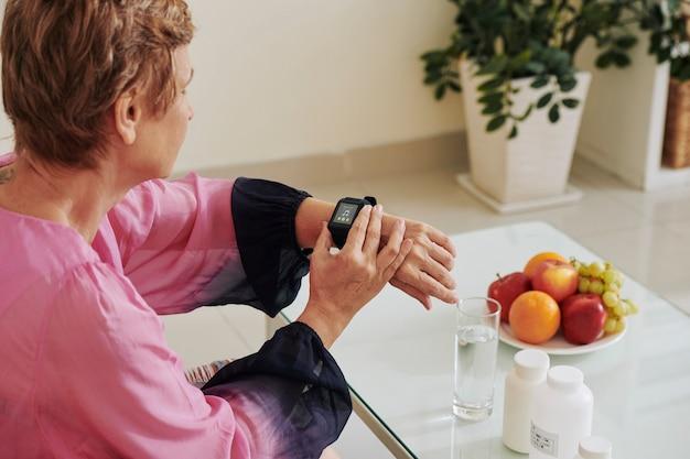 Старшая женщина, устанавливающая музыку на smartwatch