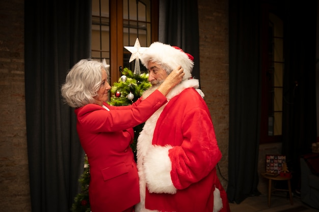 Senior woman setting up man as santa claus