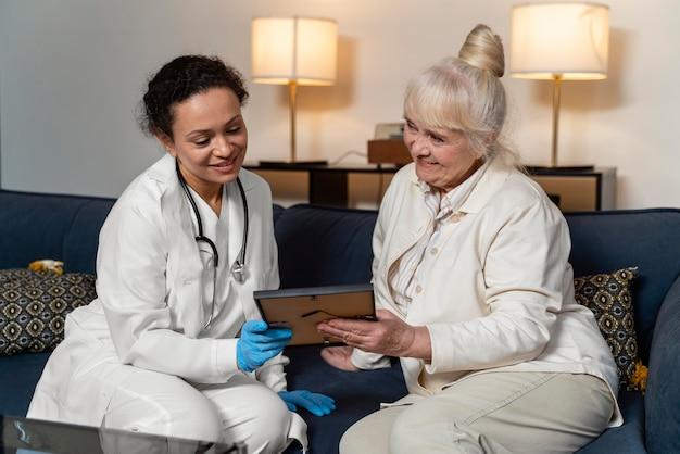 프레임에 그녀의 의사 사진을 보여주는 고위 여자