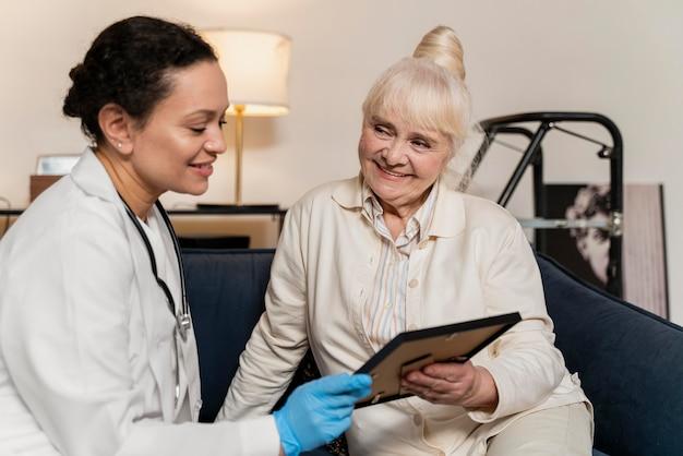 Старшая женщина показывает своему врачу фото в рамке