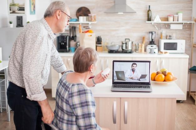 ビデオ遠隔医療会議中に医師に薬瓶を見せている年配の女性。高齢者のためのオンライン健康相談薬の症状に関する病気のアドバイス、医師の遠隔医療ウェブカメラ。医学