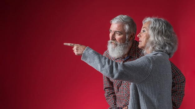 Senior woman showing something to her husband by pointing finger against red background