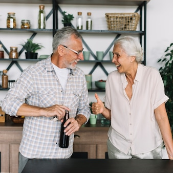 Senior woman showing thumb up gesture to her husband opening the beer bottle