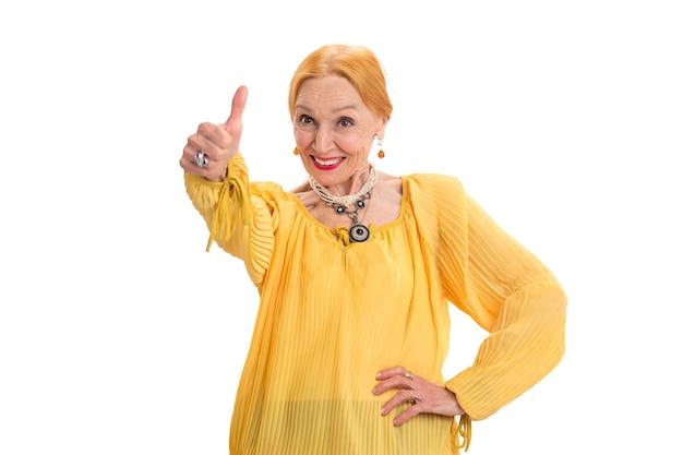 Старшая женщина показывает палец вверх леди улыбается на белом фоне, меняет ваше мышление