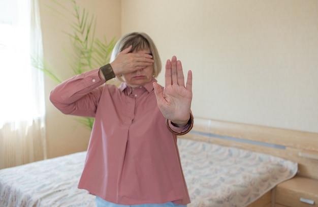 수석 여자는 그녀의 침실 배경에서 손 제스처 중지를 sigralizes. 개념의 자유, 심리적 건강, 건강한 정신