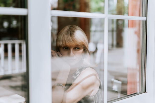 Senior woman sits in front of the window mature adult woman looking sad and thoughtful mental health