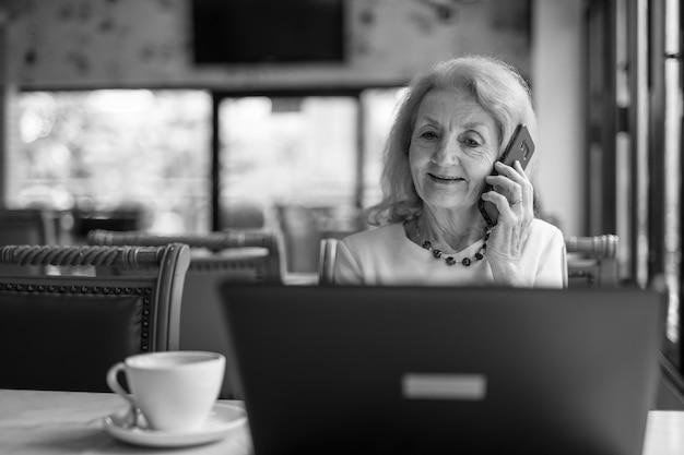 고위 여자 앉아서 노트북 컴퓨터와 휴대 전화를 사용 하여
