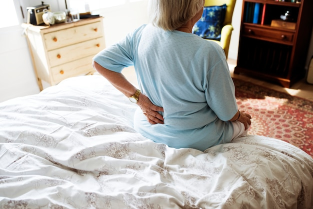 Senior woman sitting on the bed in pain