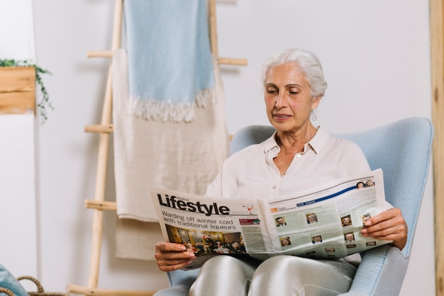 Senior woman sitting in chair reading newspaper