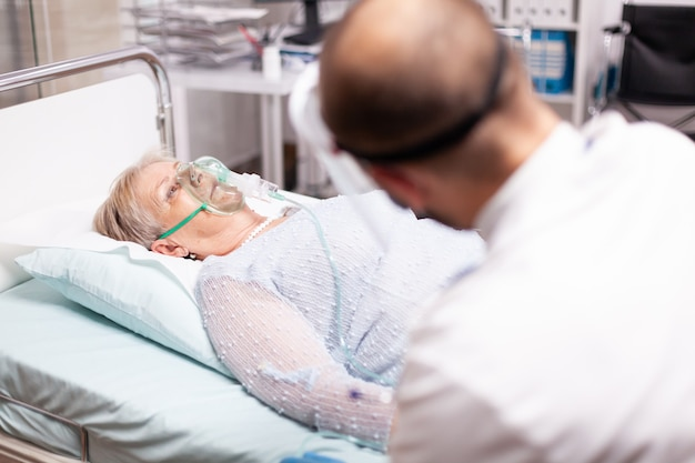 Senior woman sitting on clinic bed with oxygen mask in time of covid19