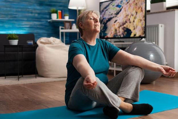 Старшая женщина, удобно сидящая в позе лотоса на коврике для йоги с закрытыми глазами, медитирует