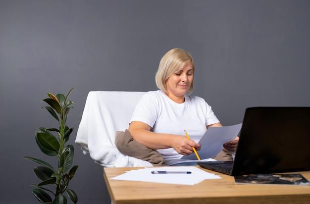집에서 안락의 자에 앉아 컴퓨터 작업 수석 여자