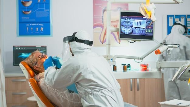 Covid-19パンデミックの間に歯の健康の世話をしている歯科医院に座っている年配の女性。防護服とフェイスシールドを身に着けたコロナウイルスの発生における新しい通常の歯科医の訪問の概念