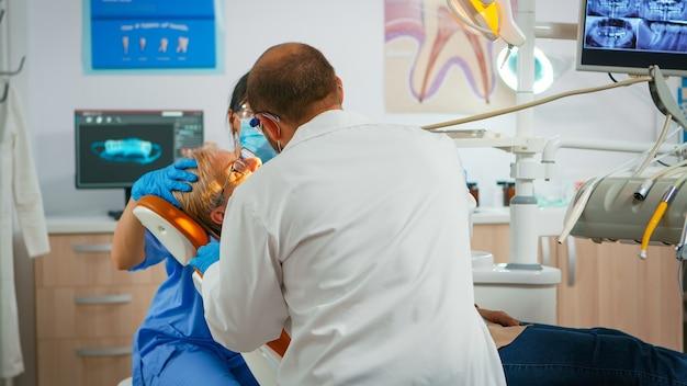 歯の健康の世話をしている歯科医院に座っている年配の女性。歯科矯正医が診察までランプを点灯し、患者が口腔病学の椅子に横になって口を開け、看護師が医者を半減させた。