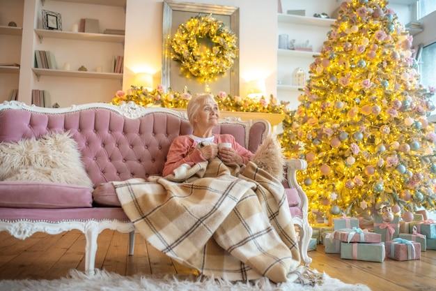 Старшая женщина, сидящая на диване с чашкой чая
