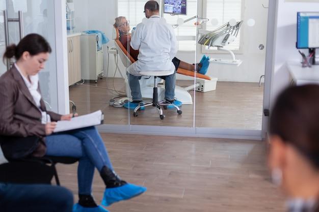 歯科医を聞いて歯科医院の椅子に座っている年配の女性