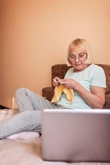 ソファに座って、自宅でウールのセーターを編む年配の女性