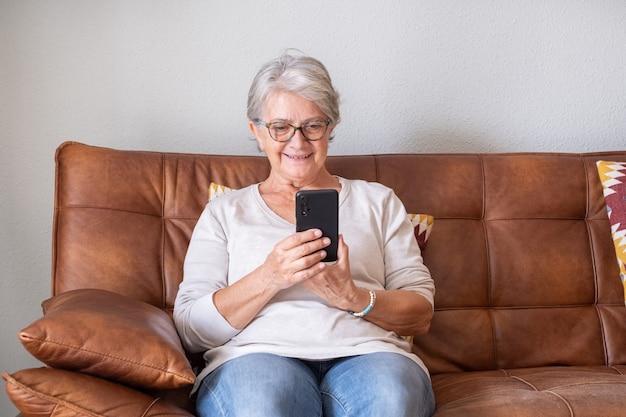 Старшая женщина, сидящая на софе и читающая текстовые сообщения на мобильном телефоне у себя дома. пожилая женщина в очках, серфинг и использование социальных сетей на мобильном телефоне в гостиной.